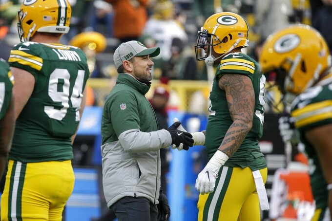 Green Bay Packers head coach Matt LaFleur talks to Preston Smith before an NFL football game against the Washington Redskins Sunday, Dec. 8, 2019, in Green Bay, Wis. (AP Photo/Mike Roemer)