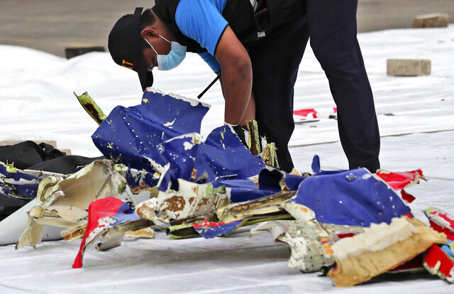An investigator of Indonesian National Transportation Safety Committee inspects parts of Sriwijaya Air Flight 182 that crashed in the waters off Java Island, at Tanjung Priok Port in Jakarta, Indonesia, Sunday, Jan. 10, 2021. Indonesian rescuers pulled out body parts, pieces of clothing and scraps of metal from the Java Sea early Sunday morning, a day after the Boeing 737-500 with dozens of people onboard crashed shortly after takeoff from Jakarta, officials said. (AP Photo/Tatan Syuflana)