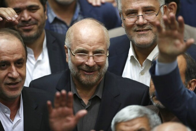 FILE - In this May 28, 2020, file photo, Mohammad Bagher Qalibaf, center, is surrounded by a group of lawmakers after being elected as speaker of the parliament, in Tehran, Iran. Iran's parliament speaker says international inspectors may no longer access images of the Islamic Republic's nuclear sites. (AP Photo/Vahid Salemi, File)