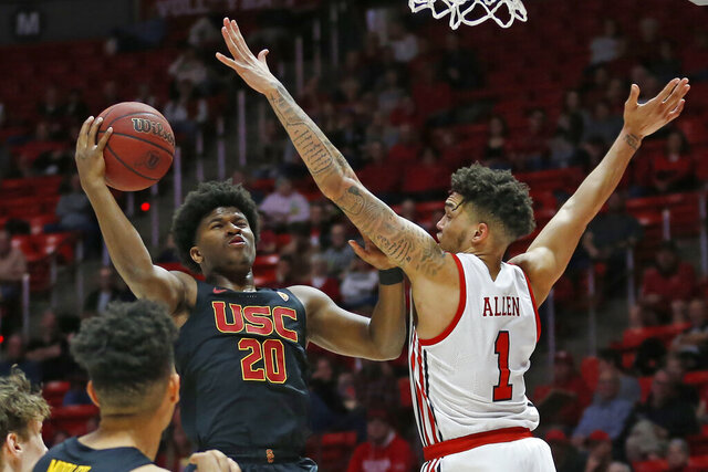 USC guard Ethan Anderson (20) goes to the basket as Utah forward Timmy Allen (1) defends in the first half of an NCAA college basketball game Sunday, Feb. 23, 2020, in Salt Lake City. (AP Photo/Rick Bowmer)