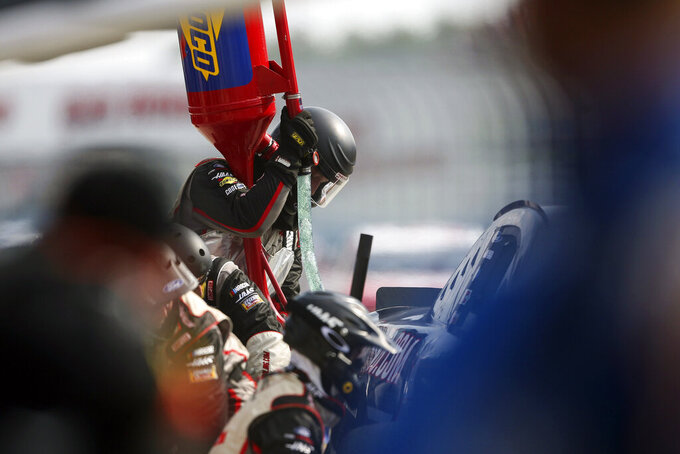 A pit crew works on Cole Custer's car during a NASCAR Cup Series auto race in Watkins Glen, N.Y., on Sunday, Aug. 8, 2021. (AP Photo/Joshua Bessex)