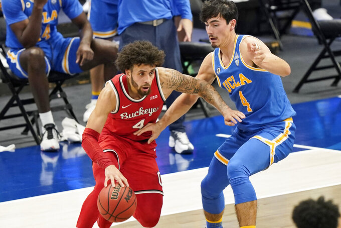 Ohio State's Duane Washington Jr., left, drives against UCLA's Jaime Jaquez Jr. in the first half of an NCAA college basketball game, Saturday, Dec. 19, 2020, in Cleveland. (AP Photo/Tony Dejak)