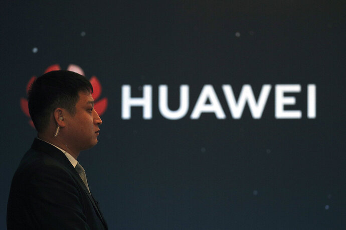 In this Jan. 9, 2019, photo, a security guard stands near the Huawei company logo during a new product launching event in Beijing. The Chinese Foreign Ministry said late Friday, Jan. 11, 2019, it is