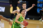 Oregon guard Will Richardson drives ahead of Southern California guard Drew Peterson (13) during the second half of a Sweet 16 game in the NCAA men's college basketball tournament at Bankers Life Fieldhouse, Sunday, March 28, 2021, in Indianapolis. (AP Photo/Jeff Roberson)