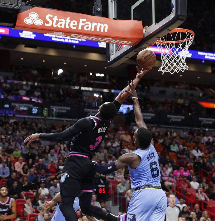 Miami Heat guard Dwyane Wade (3) scores against Memphis Grizzlies guard Shelvin Mack (6) in the second half of an NBA basketball game Saturday, Jan. 12, 2019, in Miami. (AP Photo/Brynn Anderson)
