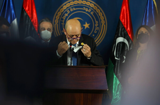 French Foreign Minister Jean-Yves Le Drian adjusts his face mask as he speaks speaks, in Tripoli, Libya, Thursday, March 25, 2021. The foreign ministers of France, Italy and Germany arrived in Tripoli Thursday, to show their support to Libya's newly elected transitional authorities, who are expected to lead the war-stricken country through general elections end of 2021. (AP Photo/Hazem Ahmed)