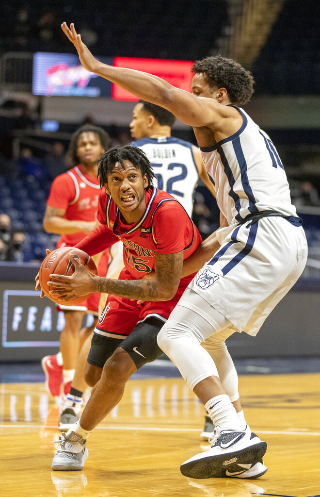 St. John's guard Vince Cole (15) drives on Butler forward Bryce Nze (10), during an NCAA college basketball game in Indianapolis, Tuesday, Feb. 9, 2021. (Robert Scheer/The Indianapolis Star via AP)