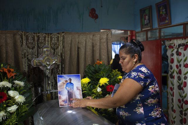 A woman places a photo of slain journalist Julio Valdivia on his casket during a wake for him inside his home in Tezonapa, Veracruz, Mexico, Thursday, Sept. 10, 2020. Valdivia's decapitated body was found five miles from Tezonapa a day earlier, and is at least the third reporter killed in the area since 2015. (AP Photo/Felix Marquez)