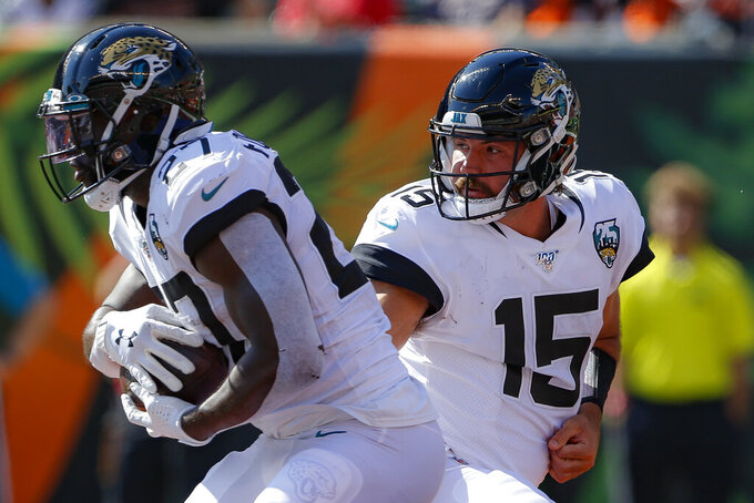 Jacksonville Jaguars quarterback Gardner Minshew (15) hands off the ball to running back Leonard Fournette (27) in the first half of an NFL football game against the Cincinnati Bengals, Sunday, Oct. 20, 2019, in Cincinnati. (AP Photo/Gary Landers)