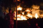 People watch as a fire burns at an auto salvage junkyard in the Kensington neighborhood of Philadelphia, Tuesday, July 10, 2018. (Joe Lamberti/Camden Courier-Post via AP)