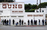 FILE - In this March 15, 2020, file photo, people wait in line to enter a gun store in Culver City, Calif. A federal judge is refusing to block Los Angeles officials from shutting down gun stores as nonessential businesses during the coronavirus pandemic. On Monday, April 6, 2020, the ruling the second time was that federal judges in California have declined to intervene in shutdown orders even as similar orders are being challenged nationwide. (AP Photo/Ringo H.W. Chiu, File)