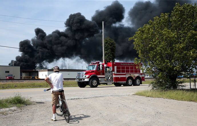 A resident watches as a firetruck arrives in downtown Dupo, Ill. to help fight a tanker fire from a derailed train on Tuesday, Sept. 10. 2019. Black smoke coming from the derailment scene can be seen for miles and caused the evacuation of schools in the town, authorities said. (Robert Cohen/St. Louis Post-Dispatch via AP)