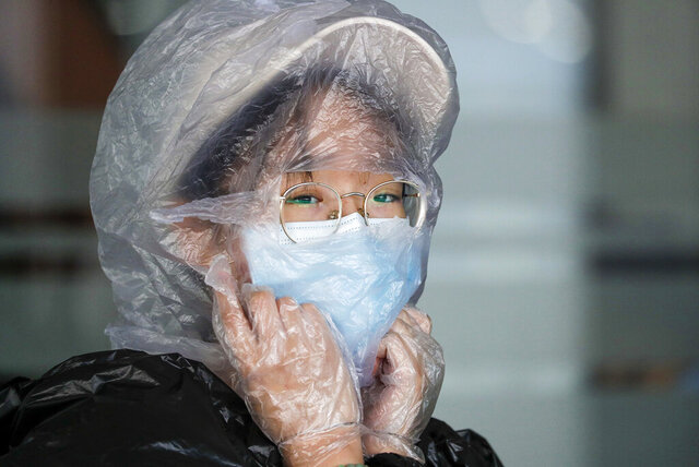 FILE - In this March 18, 2020, file photo, a Chinese woman uses a plastic bag to cover her head while waiting for her flight at the departure area of Manila's International Airport, Philippines. As governments across the world enact emergency measures to keep people at home and stave off the pandemic, some are unhappy about having their missteps publicized. Others are taking advantage of the crisis to silence critics and tighten control. (AP Photo/Aaron Favila, File)