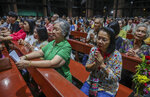 In this Friday, Oct. 18, 2019, photo, Catholics pray during the 30th anniversary of the beatification of the Seven Martyrs in the Christ Church in Songkhon village, Mukdahan province, northeastern of Thailand. There are about 388,000 Catholics in Thailand, representing 0.58 percent of the country's 69 million population. (AP Photo/Sakchai Lalit)