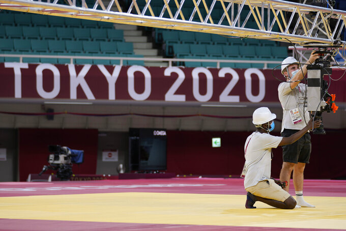 Workers adjust a camera on the field of play for judo at the Nippon Budokan ahead of the 2020 Summer Olympics, Friday, July 23, 2021, in Tokyo, Japan. (AP Photo/Vincent Thian)