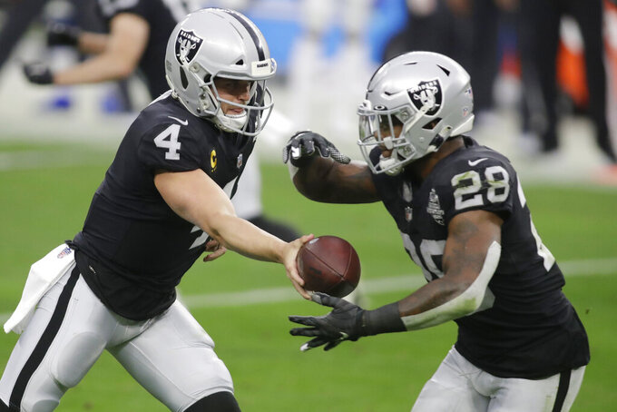 Las Vegas Raiders quarterback Derek Carr (4) hands off to running back Josh Jacobs (28) during the first half of an NFL football game against the Indianapolis Colts, Sunday, Dec. 13, 2020, in Las Vegas. (AP Photo/Isaac Brekken)