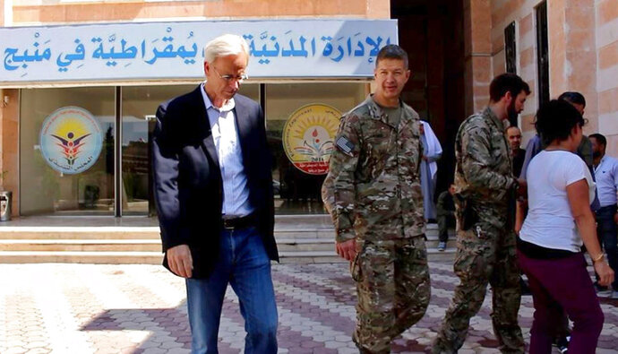 This photo released by Hawar News, the news agency for the semi-autonomous Kurdish areas in Syria, shows the anti-IS U.S. coalition, Maj. General James Jarrard, center, and veteran Middle East diplomat William Roebuck, left, in the town of Manbij, in Aleppo province, Syria, Thursday, June 7, 2018. The US delegation's visit comes days after a delicate U.S-Turkish deal that is expected to see an American-backed Kurdish militia pull out of the area. The sign in Arabic in the background reads,