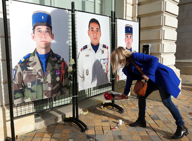 A woman lays flowers under portraits of French soldiers, Alex Morisse, left, Romain Salles de Saint Paul, center, and Nicolas Regard at the town hall of Pau, southwestern France, Wednesday, Nov. 27, 2019. Two helicopters collided on a moonless night and killed 13 French soldiers fighting Islamic State group-linked extremists in Mali, France said Tuesday, mourning its highest military death toll in nearly four decades. (AP Photo/Bob Edme)