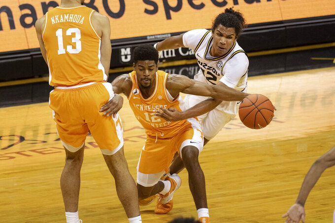 Tennessee's Victor Bailey Jr., center, drives past teammate Olivier Nkamhoua, left, and Missouri's Dru Smith, right, during the first half of an NCAA college basketball game Wednesday, Dec. 30, 2020, in Columbia, Mo. (AP Photo/L.G. Patterson)