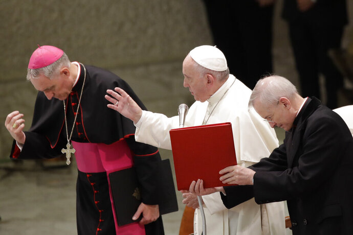 Pope Francis delivers his blessing in the Paul VI Hall at the Vatican at the end of an audience with students and teachers of the LUMSA Catholic University, Thursday, Nov. 14, 2019. (AP Photo/Alessandra Tarantino)