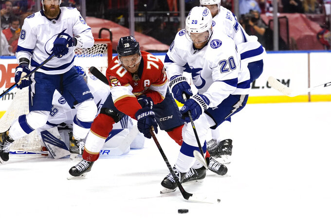Florida Panthers right wing Patric Hornqvist (70) and Tampa Bay Lightning center Blake Coleman (20) go for the puck during the second period in Game 2 of an NHL hockey Stanley Cup first-round playoff series, Tuesday, May 18, 2021, in Sunrise, Fla. (AP Photo/Lynne Sladky)