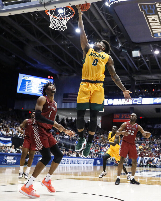 North Dakota State's Vinnie Shahid (0) shoots as North Carolina Central's Zacarry Douglas (1) watches during the second half of a First Four game of the NCAA men's college basketball tournament Wednesday, March 20, 2019, in Dayton, Ohio. (AP Photo/John Minchillo)