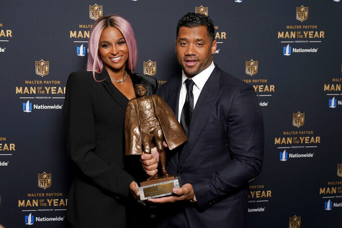 Seattle Seahawks quarterback Russell Wilson and his wife Ciara pose for a photo after Wilson won the Walter Payton NFL Man of the Year awards at the NFL Honors ceremony as part of Super Bowl 55 Friday, Feb. 5, 2021, in Tampa, Fla. (AP Photo/Charlie Riedel)