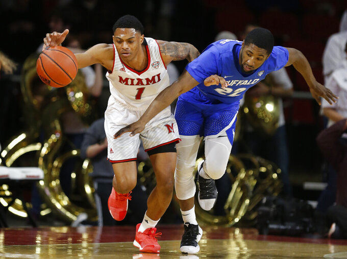 Miami (Ohio) guard Nike Sibande (1) and Buffalo guard Dontay Caruthers, right, chase a loose ball during the first half of an NCAA college basketball game, Friday, March 1, 2019, in Oxford, Ohio. (AP Photo/Gary Landers)