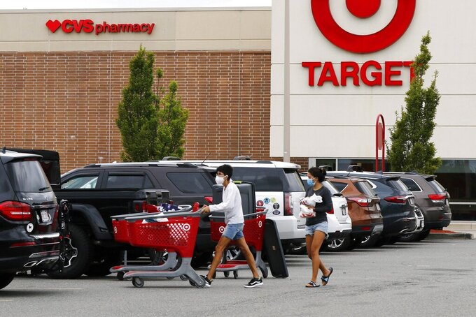 FILE - In this Aug. 4, 2020 file photo, shoppers take purchases to their vehicle in the parking lot of a Target store in Marlborough, Mass.  Target's strong sales streak extended through the holiday season, as shoppers snapped up everything from clothing to home goods during the pandemic. The Minneapolis company reported Wednesday, Jan. 13, 2021, that its online sales surged 102% for the November and December period. (AP Photo/Bill Sikes)