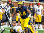 Michigan linebacker Cameron McGrone (44) celebrates his sack of Iowa quarterback Nate Stanley, bottom, in the fourth quarter of an NCAA college football game in Ann Arbor, Mich., Saturday, Oct. 5, 2019. Michigan won 10-3. (AP Photo/Tony Ding)