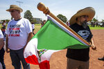Fernando Montoya, right, waves a Mexican flag to protest the visit of President Donald Trump to the border city after the Aug. 3 mass shooting in El Paso, Texas, Wednesday, Aug. 7, 2019.  Trump headed to El Paso, after visiting  Dayton, Ohio on Wednesday to offer a message of healing and unity, but he will be met by unusual hostility in both places by people who fault his own incendiary words as a contributing cause to the mass shootings.  (AP Photo/Andres Leighton)
