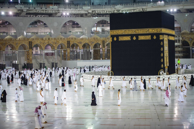 CLARIFIES THAT THE UMRAH PILGRIMAGE CAN BE UNDERTAKEN AT ANY TIME OF THE YEAR -- In this photo released by Saudi Ministry of Hajj and Umrah, Muslims practice social distancing while praying around the Kaaba, the cubic building at the Grand Mosque during the first day umrah pilgrimages were allowed to restart, in the Muslim holy city of Mecca, Saudi Arabia, Sunday, Oct. 4, 2020. The umrah pilgrimage, or smaller pilgrimage, can be undertaken at any time of the year. A very small, limited number of people donning the white terrycloth garment symbolic of the Muslim pilgrimage circled Islam's holiest site in Mecca on Sunday after Saudi Arabia lifted coronavirus restrictions that had been in place for months. (Saudi Ministry of Hajj and Umrah via AP)