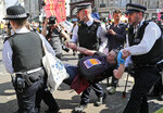 Police arrest protestors at Oxford Circus in London, Friday, April 19, 2019. The group Extinction Rebellion is calling for a week of civil disobedience against what it says is the failure to tackle the causes of climate change. (AP Photo/Frank Augstein)