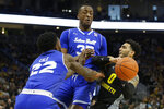 Marquette's Markus Howard (0) drives to the basket against Seton Hall's Romaro Gill and Myles Cale (22) during the first half of an NCAA college basketball game Saturday, Feb. 29, 2020, in Milwaukee. (AP Photo/Aaron Gash)