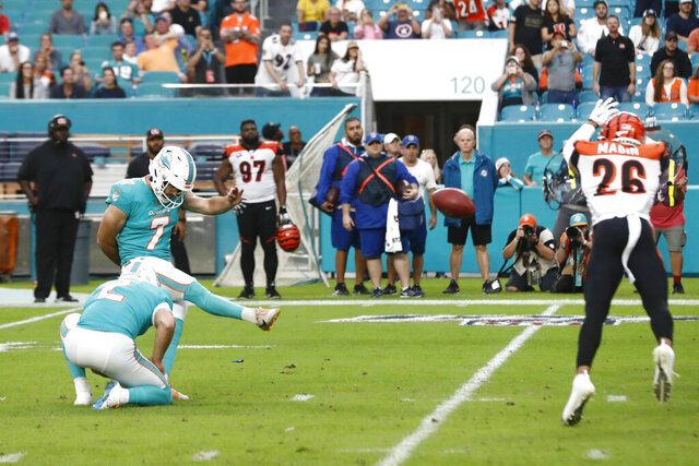 Miami Dolphins kicker Jason Sanders (7) kicks the game-winning field goal, as Cincinnati Bengals cornerback Greg Mabin (26) attempts to block, during overtime at an NFL football game, Sunday, Dec. 22, 2019, in Miami Gardens, Fla. The Dolphins defeated the Begals 38-35. (AP Photo/Brynn Anderson)