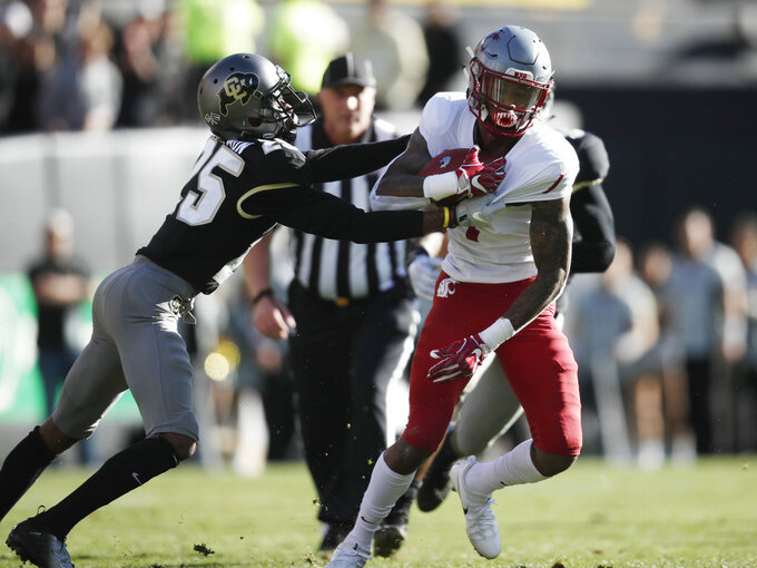 Colorado cornerback Mekhi Blackmon, left, grabs the jersey of Washington State wide receiver Davontavean Martin as he gains yardage after pulling in a pass in the first half of an NCAA college football game Saturday, Nov. 10, 2018, in Boulder, Colo. (AP Photo/David Zalubowski)