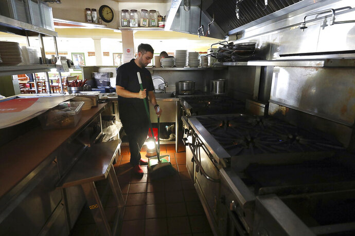 Salvador Espinosa sweeps in the kitchen of a Mary's Pizza Shack restaurant during a Pacific Gas and Electric Co. power shutdown in Santa Rosa, Calif., Thursday, Oct. 10, 2019. More than 1.5 million people in Northern California were in the dark Thursday, most for a second day, after the state's biggest utility shut off electricity to many areas to prevent its equipment from sparking wildfires as strong winds sweep through the region. (Christopher Chung/The Press Democrat via AP)