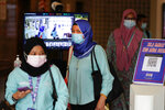 Employees wearing face masks to help curb the spread of the coronavirus leave their office in Kuala Lumpur, Malaysia, Monday, Oct. 26, 2020. Senior Minister Ismail Sabri Yaakob announce conditional movement control order (MCO) in Kuala Lumpur, Selangor and Putrajaya will be extended for another two weeks until Nov 9. (AP Photo/Vincent Thian)