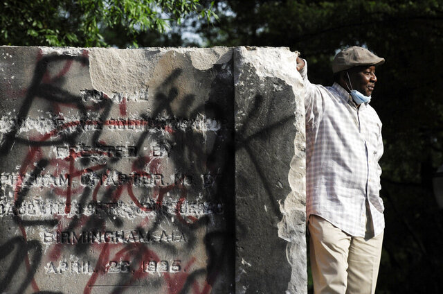 Robert Walker poses for a photograph on the remains of a Confederate memorial that was removed overnight in Birmingham, Ala., on Tuesday, June 2, 2020. The city took down the more than 50-foot-tall obelisk following protests over the police death of George Floyd and a night of vandalism in the city. (AP Photo/Jay Reeves)