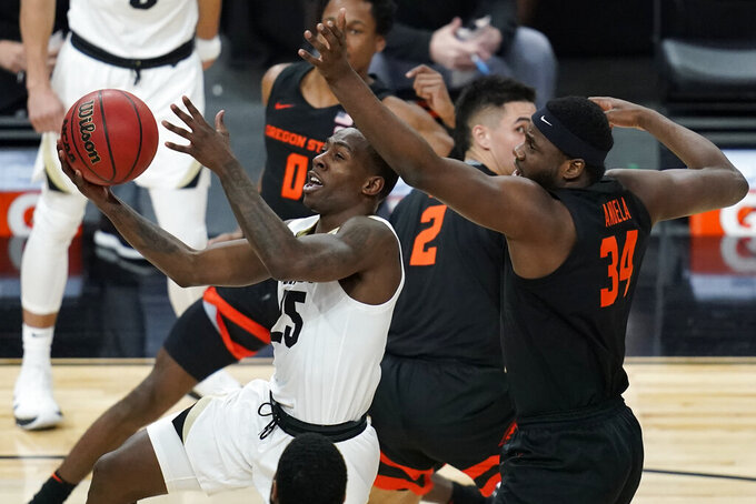 Colorado's McKinley Wright IV (25) shoots around Oregon State's Rodrigue Andela (34) during the first half of an NCAA college basketball game in the championship of the Pac-12 men's tournament Saturday, March 13, 2021, in Las Vegas. (AP Photo/John Locher)