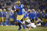 FILE - In this Nov. 2, 2019 file photo, UCLA quarterback Dorian Thompson-Robinson, left, runs while pursued by Colorado linebacker Nate Landman during the first half of an NCAA college football game in Pasadena, Calif. He is returning for this third season as quarterback. (AP Photo/Kelvin Kuo, File)