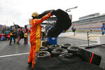A crew member for driver Kyle Busch covers tires during a rain delay at a NASCAR Cup Series auto race at Charlotte Motor Speedway Sunday, May 24, 2020, in Concord, N.C. (AP Photo/Gerry Broome)