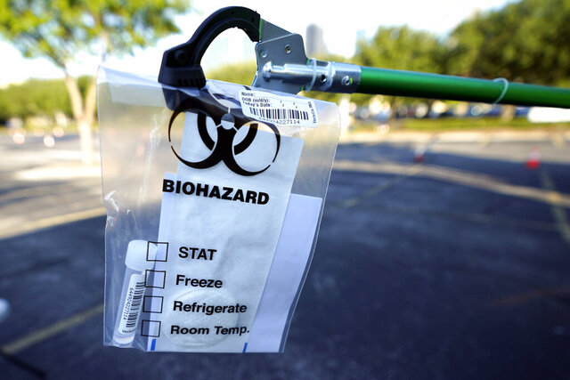 A test kit is displayed at a Texas Division of Emergency Management free COVID-19 testing site at Minute Maid Park Saturday, Aug. 8, 2020, in Houston. The newly opened mega site, which has eight drive-thru lanes and four walk-up lanes, has the ability to process 2,000 tests per day. (AP Photo/David J. Phillip)