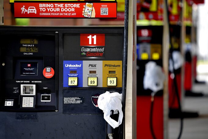 FILE - In this May 11, 2021 file photo, a QuickTrip convenience store has bags on their pumps as the station has no gas, in Kennesaw, Ga. On Friday, May 14, The Associated Press reported on stories circulating online claiming to show photos of Americans filling their cars with plastic bags of gasoline and lining up at gas stations with red gas cans in recent days. Social media users are misrepresenting old photos to falsely suggest they show Americans stockpiling gasoline this week after a hack of the Colonial Pipeline led to thousands of gas stations running out of fuel to due to distribution problems and panic-buying. (AP Photo/Mike Stewart, File)
