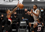 San Antonio Spurs center LaMarcus Aldridge, right , passes the ball against Portland Trail Blazers guard Damian Lillard, left, during the second half of an NBA basketball game in Portland, Ore., Monday, Jan. 18, 2021. (AP Photo/Steve Dykes)