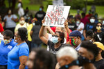 FILE - In this May 16, 2020, file photo, a woman holds a sign during a rally to protest the shooting of Ahmaud Arbery, in Brunswick, Ga. Arbery was shot and killed in February by two men who told police they thought he was a burglar. (AP Photo/Stephen B. Morton, File)