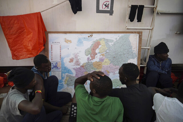 In this Sept. 23, 2019 photo, rescued migrants look at a map of Europe aboard the Ocean Viking humanitarian ship as it sails in the Mediterranean Sea. The misery of migrants in Libya has spawned a thriving and highly lucrative business, in part funded by the EU and enabled by the United Nations, an Associated Press investigation has found. (AP Photo/Renata Brito)