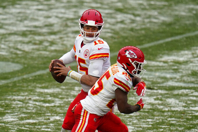 Kansas City Chiefs quarterback Patrick Mahomes looks to throw a pass as running back Clyde Edwards-Helaire fakes the handoff during the second half of an NFL football game against the Denver Broncos, Sunday, Oct. 25, 2020, in Denver. (AP Photo/Jack Dempsey)