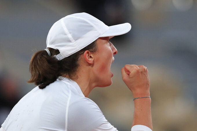 Poland's Iga Swiatek celebrates winning her fourth round match of the French Open tennis tournament against Romania's Simona Halep in two sets, 6-1, 6-2, at the Roland Garros stadium in Paris, France, Sunday, Oct. 4, 2020. (AP Photo/Michel Euler)