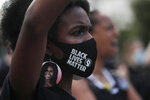 A woman wears earrings depicting First Lady Michelle Obama during a protest against racial injustice outside the White House from a section of 16th Street that's been renamed Black Lives Matter Plaza, Saturday, July 4, 2020, in Washington.(AP Photo/Maya Alleruzzo)